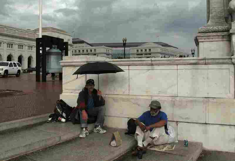 A storm moves in.  Panhandlers Michael Allen (l) and Rod Amis take shelter beside the fountain at Columbus Circle.
