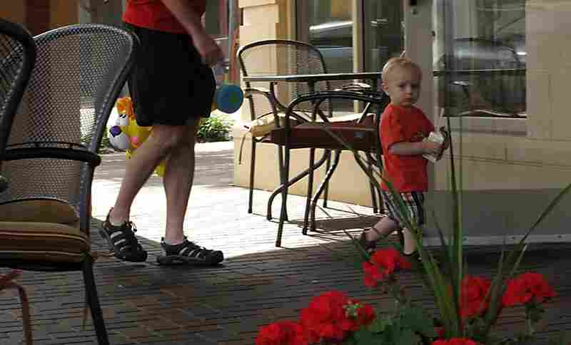 Axel McAhren checks out the cafe as he takes his morning constitutional. His father Scott provides logistical support.