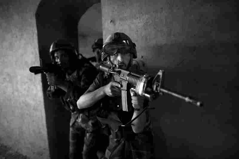 Commandos clear a mock house during a training session.