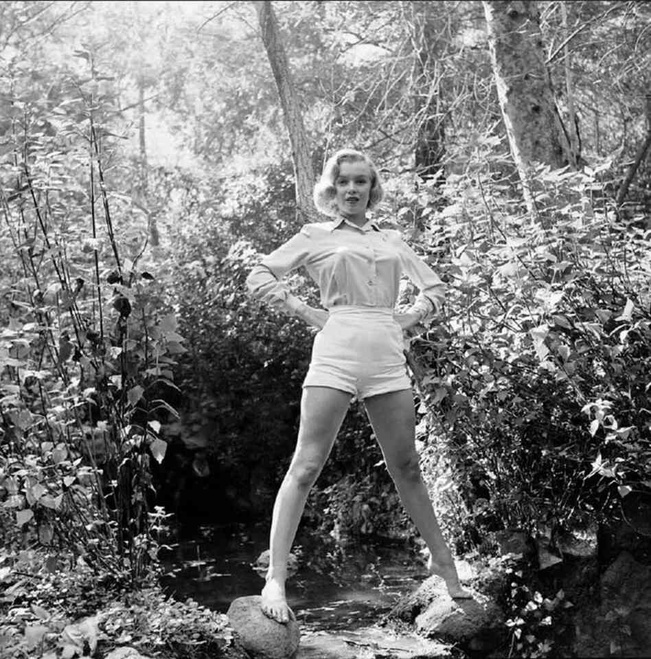 "A barefoot Monroe balances on rocks over a tiny brook. In a 1999 interview with Digital Journalist, photographer Ed Clark described how in 1950 he received a call from a friend at 20th Century Fox about ""a hot tomato"" the studio had just signed: Marilyn Monroe."