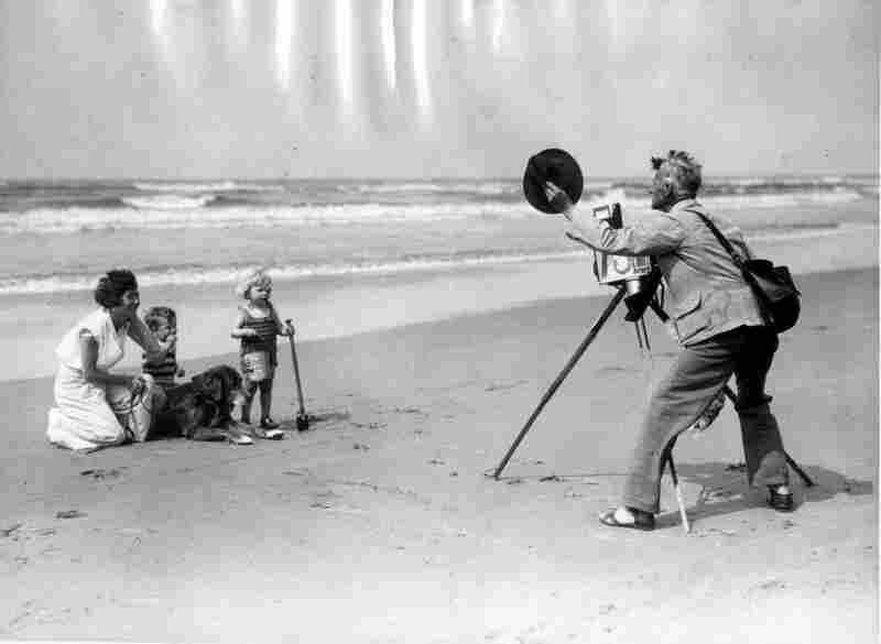 A beach photographer takes a portrait of a mother and her two children, Netherlands, circa 1930.