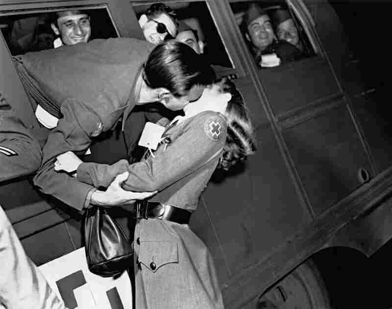An American soldier steals a kiss from a Red Cross volunteer, World War II, United States, 1942.