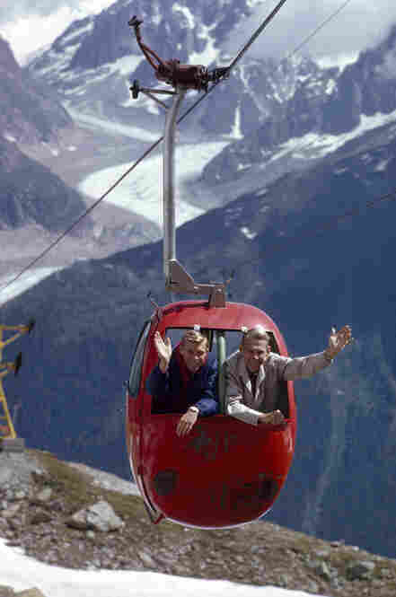 A man and his son ride a cable car in the Alps with Mer de Glace Glacier and Mont Blanc as a background.
