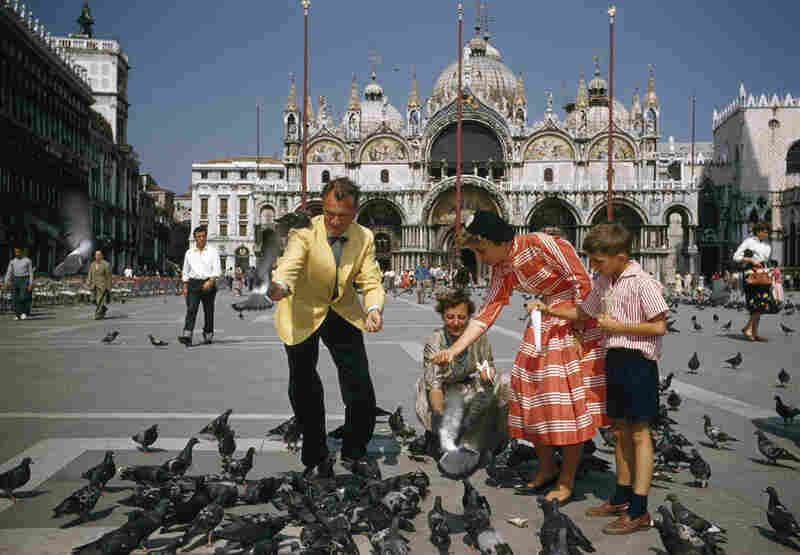In 1957, tourists feed pigeons in Venice's St. Mark's Square.