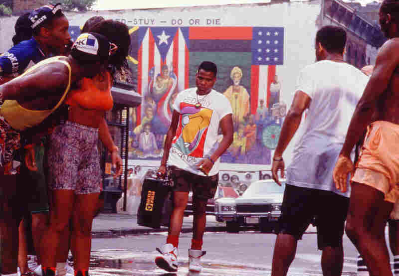 "Radio Raheem, (Bill Nunn), who makes his presence known with a monolithic boombox blaring Public Enemy's ""Fight The Power,"" provokes the film's climax.  He and Buggin' Out (Giancarlo Esposito) protest Sal's Wall of Fame, which leads Sal to smash Radio's boombox. This prompts a riot, and Radio is ultimately killed by the police.  As a result, the pizzeria is burned to the ground."
