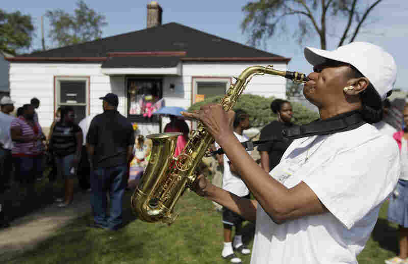 Erine D. Shelby plays Jackson tunes on her saxophone as mourners gather outside the pop star's boyhood home in Gary, Ind., Thursday.