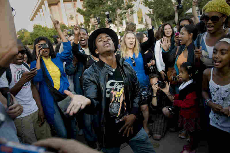 Some fans, such as Marlon Russ (center), express their grief by dancing and singing outside the UCLA Medical Center on Thursday.