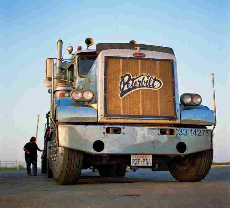 A driver checks the trailer load on his Peterbilt truck.