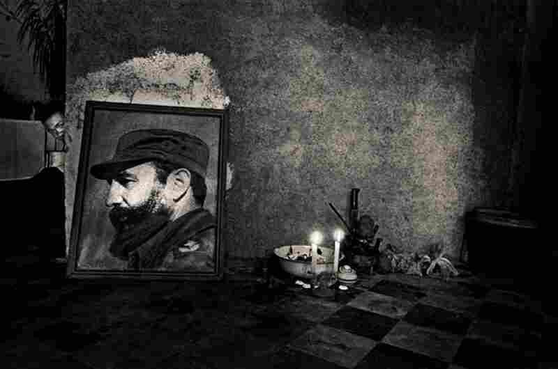 A man peers around the corner at a Santeria altar, Havana, 1995.