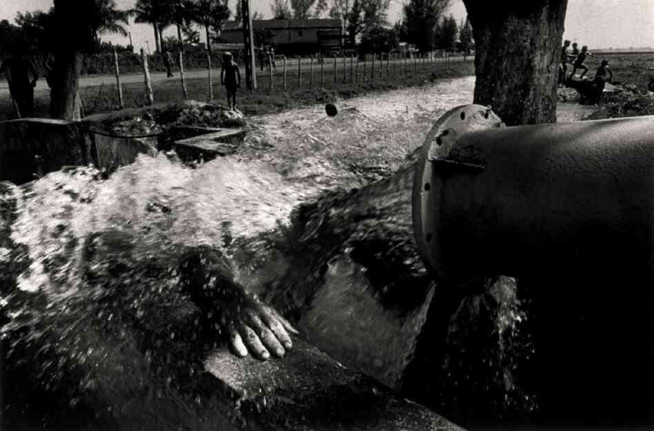A man showers on a hot summer day, near Giron, 1996.