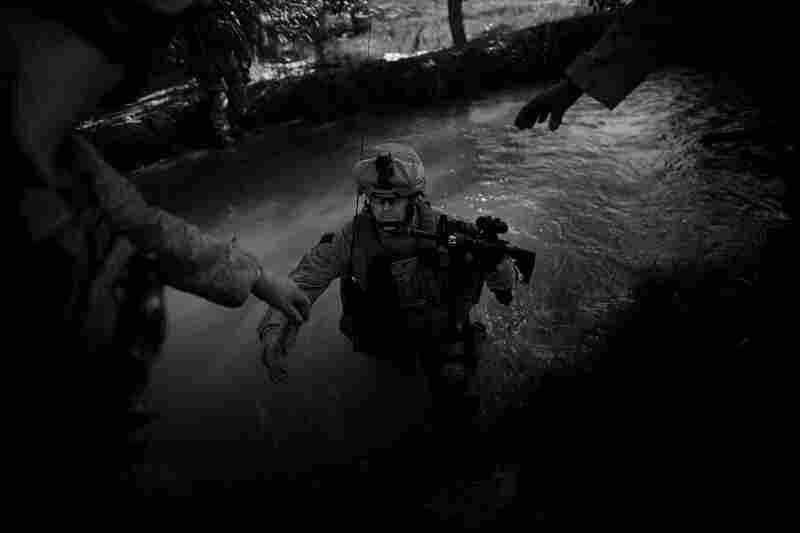 Lance Cpl. Daron Diepenbruck wades through one of the hundreds of irrigation ditches the Marines had to cross. Gilkey says that the terrain in the Helmand province feels more like Vietnam than Afghanistan.