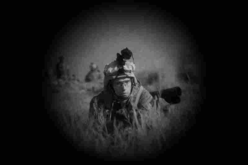 In this night vision photograph, Marines attempt to determine a route across the rugged terrain.  At night, temperatures remain in the 90s. But the Marines eventually acclimate to the high temperatures, so nights feels cool.  The sun rises again around 4 a.m.