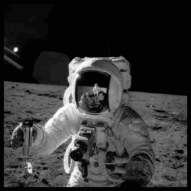 Alan Bean holding lunar soil sample container at Sharp Crater, photographed by Charles Conrad, Apollo 12, Nov. 14-24, 1969