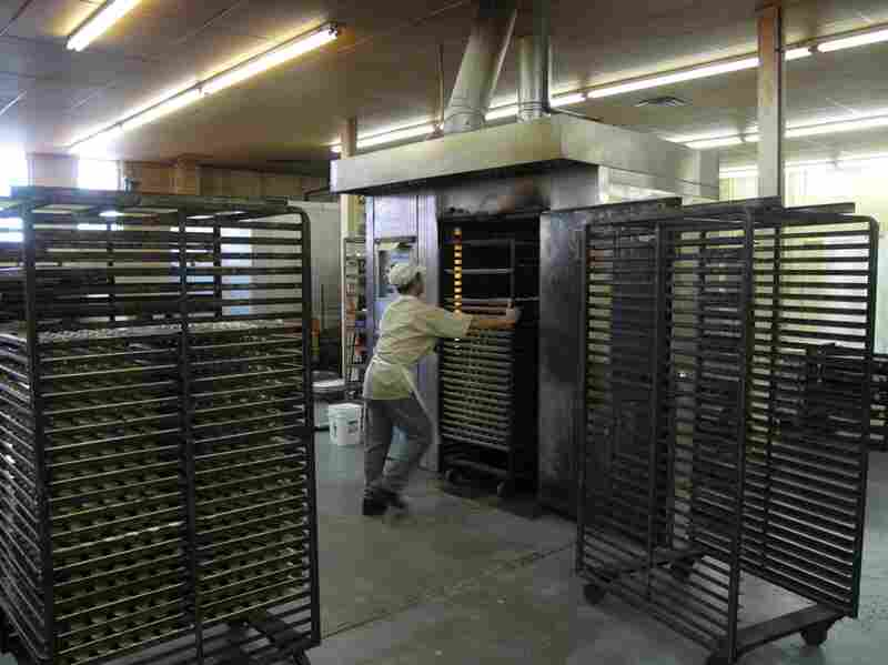 Racks of raw cookies get rolled into a giant freestanding oven.