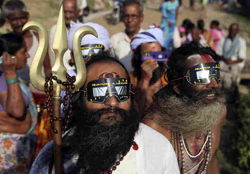 The longest solar eclipse of the 21st century began in India just after dawn Wednesday. Here, Hindu holy men watch through specially designed viewing glasses in Allahabad, India.