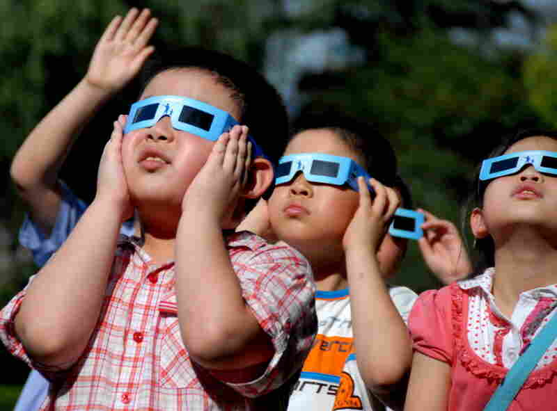 Children in Shanghai await the solar eclipse with special sunglasses.