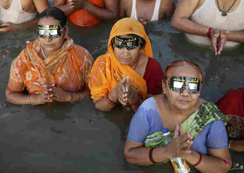 Hindu devotees observe a solar eclipse through specially designed viewing glasses as they take holy dips in the Sangam river in Allahabad, India.
