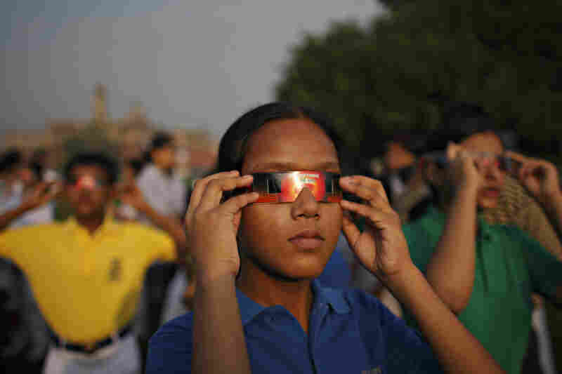 Indian schoolchildren hold up protective eye goggles to view a solar eclipse over New Delhi on Wednesday. Only a partial eclipse was visible from the Indian capital.