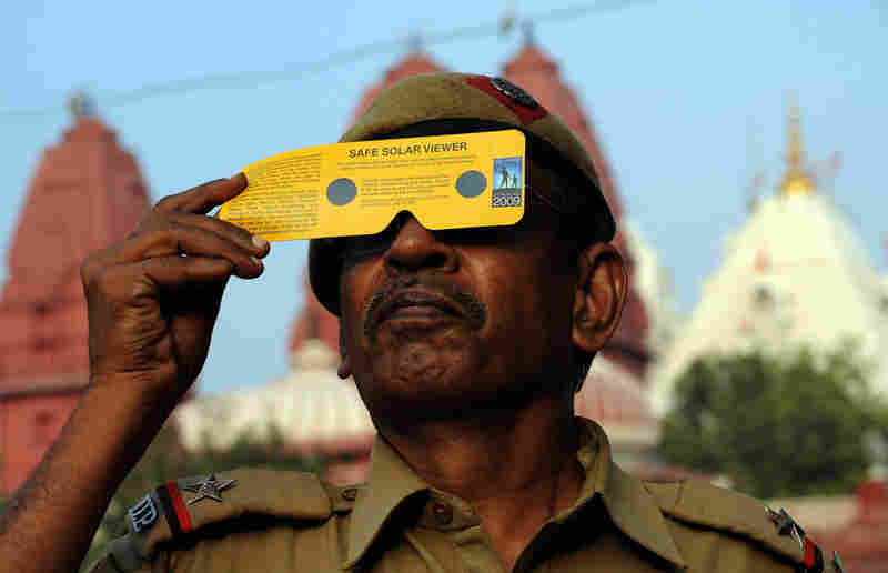 An Indian police officer watches the partial solar eclipse through solar viewing goggles in New Delhi.