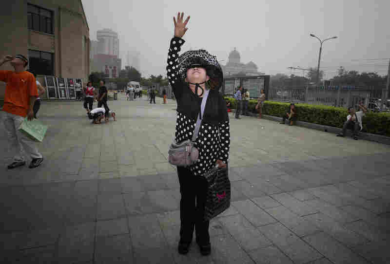 A Chinese woman reaches for the sky as she looks at a partial solar eclipse outside the planetarium in Beijing.