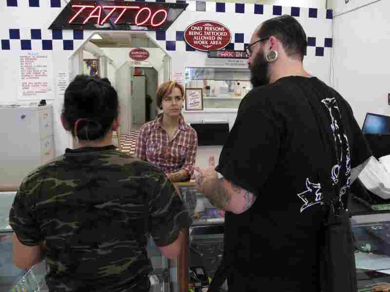 Tattoo and piercing artist Tina Pell listens to two guys trying to sell her a line of body piercing jewelry.  The guy on the right is clearly experienced with both piercing and tattoos.