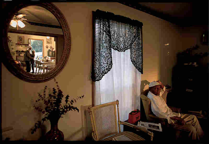 Lateef Muhammed, 76, relaxes in New Medinah, Miss., as his granddaughter and wife are reflected in the mirror. New Medinah, located near Sumrall, Miss., and founded by African-American Sunni Muslims in the 1980s, is a village of more than 20 families. November 2002.