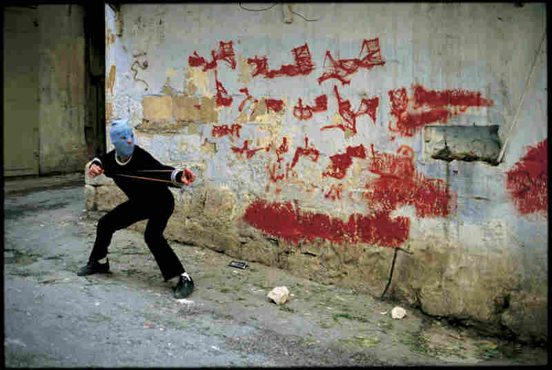 A boy aims his slingshot at Israeli soldiers in the Nablus casbah, which was shut down by striking shopkeepers. West Bank, March 1998.