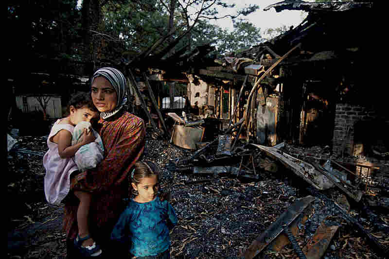 Janeth Hammid and her children stand in the ruins of the mosque in Savannah, Ga., which was torched by an unknown arsonist. September 2003.