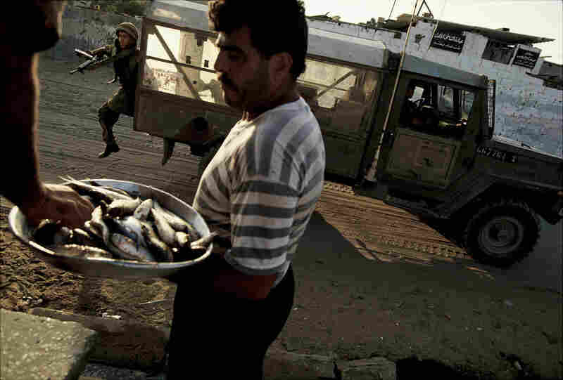 A man sells fish as an Israeli soldier jumps from his truck to chase Palestinians who had been throwing stones in Gaza City, July 1993.