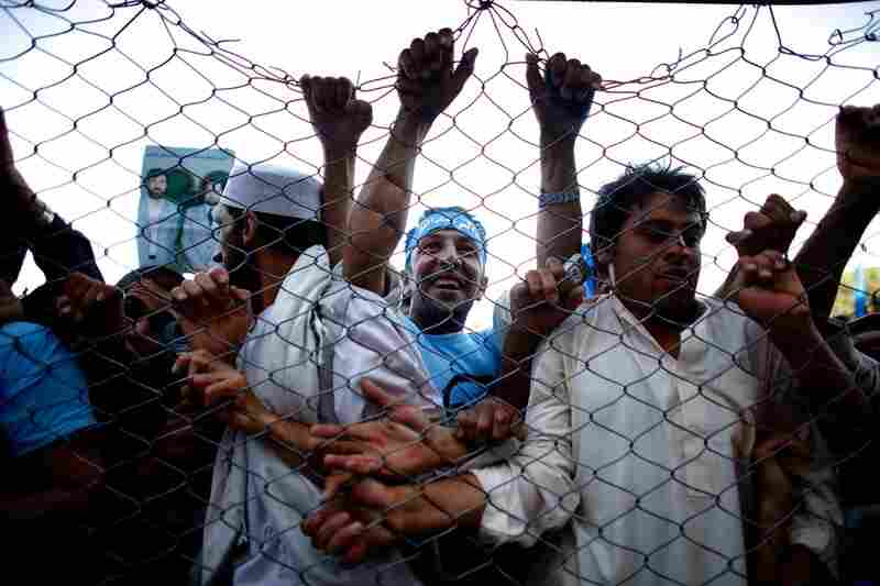 The rally in Herat quickly fills up, and Abdullah's supporters press against a fence for a better view.