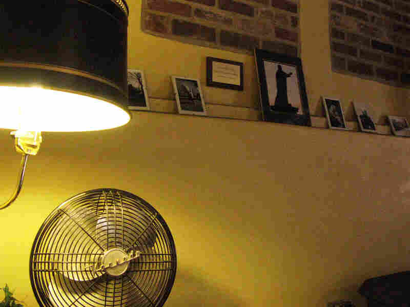 An antique fan on a desk in the Saint Vincent Gristmill Coffeehouse, where a lamp illuminates pictures of the area's landmarks — among them a statue of archabbey founder Boniface Wimmer.