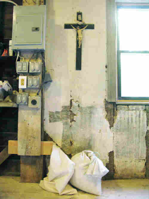 A crucifix hangs on the wall above bags of flour in the Saint Vincent Gristmill.