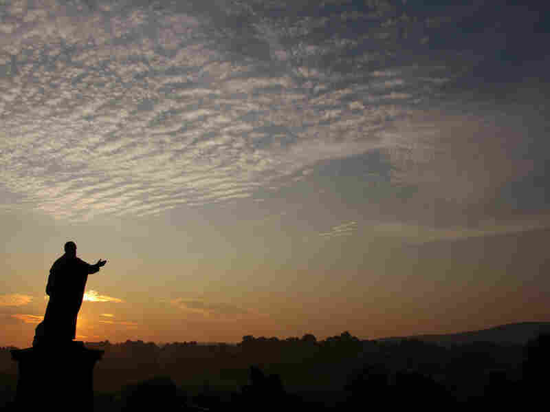 The sun rises in Latrobe, Pennsylvania behind a statue of Archabbot Boniface Wimmer, who founded the Saint Vincent Archabbey in 1846.  It shares a home with St. Vincent College.