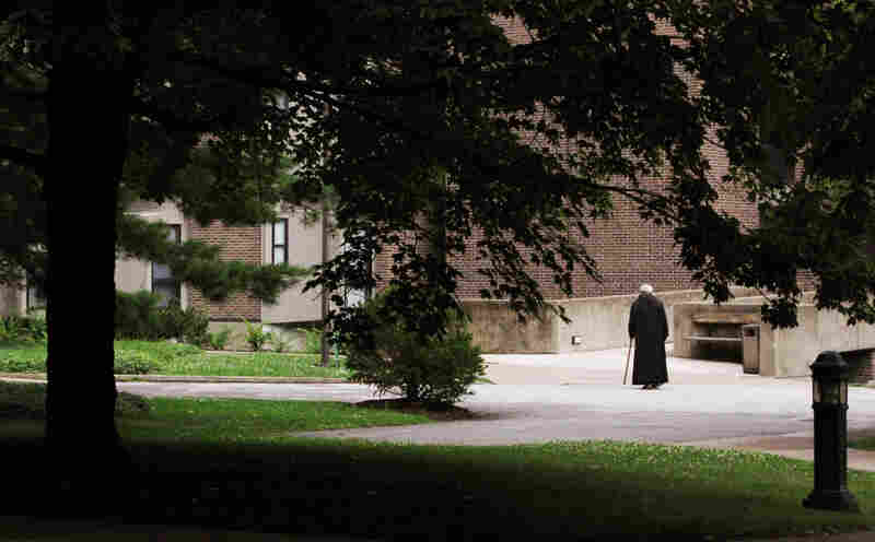 A monk walks with a cane outside the monastery at the Saint Vincent Archabbey.