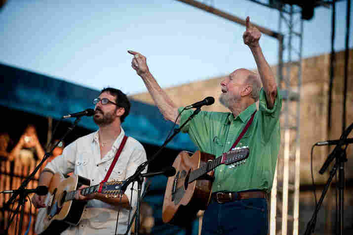 Pete Seeger directs the crowd.