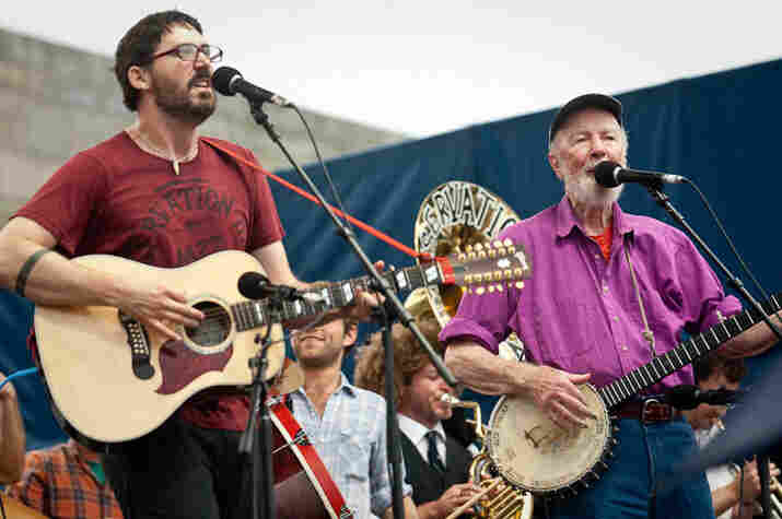 """Now backed by Ben Jaffe's tuba (of Preservation Hall Jazz Band fame), Tao Rodriguez and Pete Seeger lead a rousing version of """"When the Saints Go Marching In."""""""