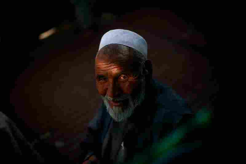 An ethnic Hazara man sits on the porch of a tea shop on the southwestern edge of Kabul, Afghanistan's capital. The Hazara minority is poised to play a key role in the Aug. 20 presidential elections and provincial council races.