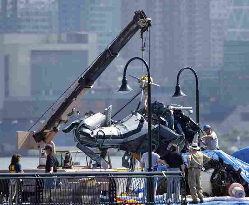 The wreckage of a helicopter is repositioned by a crane on a pier in Hoboken, N.J., Monday. The helicopter was hit by a small plane Saturday and fell into the Hudson River between New York and New Jersey. On Monday, search crews were still trying to recover the bodies of two of nine people killed.