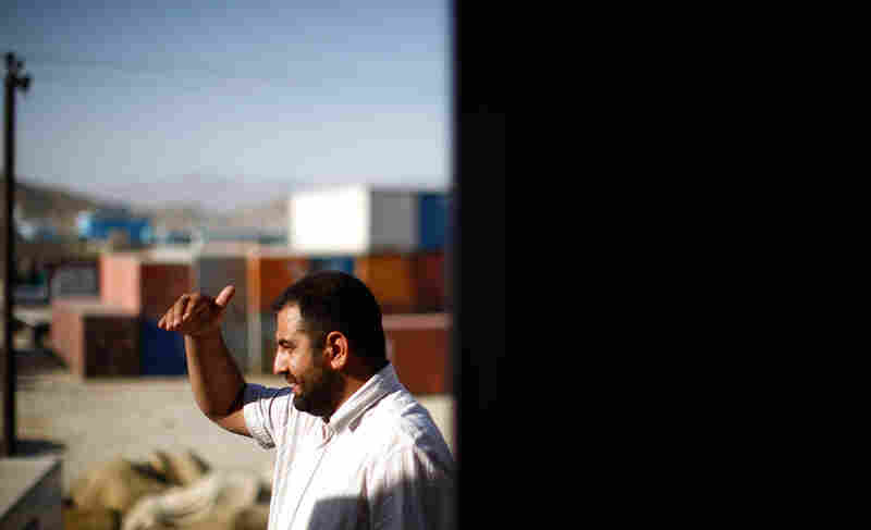 Shafi Noorzi looks out over his truck terminal from the dispatcher's office in Kabul.