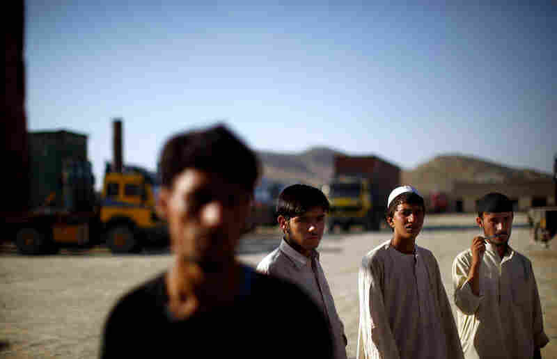 Shafi Noorzi's employees look over the incoming fleet of trucks.