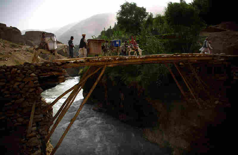 Donkeys, their handlers and the Afghan National Police escort a load of voting materials over a handmade bridge en route to the village of Quali Kuana.