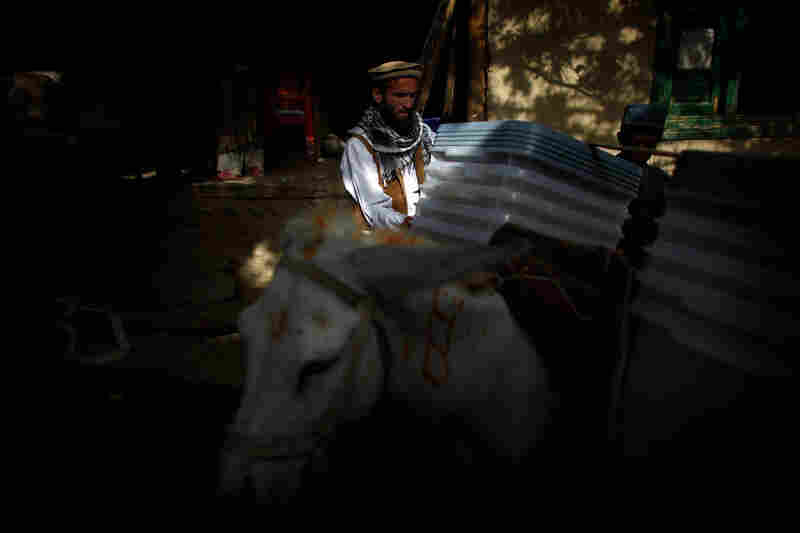 Election materials are unloaded at a private home of a local elder in the village of Quali Kuana, where the ballots will be guarded by the Afghan National Police. Security accompanies all of the voting materials no matter how remote the village. The ballots will be escorted back to Kabul via donkey and truck.