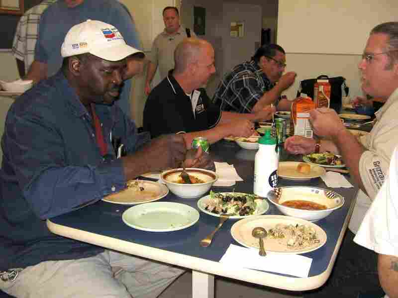 Reggie Russell (left foreground) eats a meal carefully prepared in Hammack's kitchen at the Bay Area Rescue Mission in Richmond, Calif.