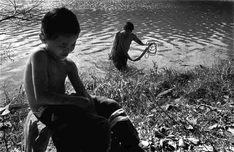 A boy waits for his father to finish fishing in a contaminated lagoon.
