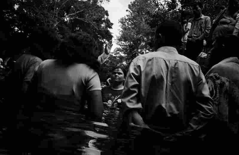 A baptism is performed at a local swimming area in the city of Chalchuapa. Evangelical churches have gained popularity in the postwar era. A large percentage of Salvadorans have changed religions, mainly from Catholic to evangelical Protestant denominations.