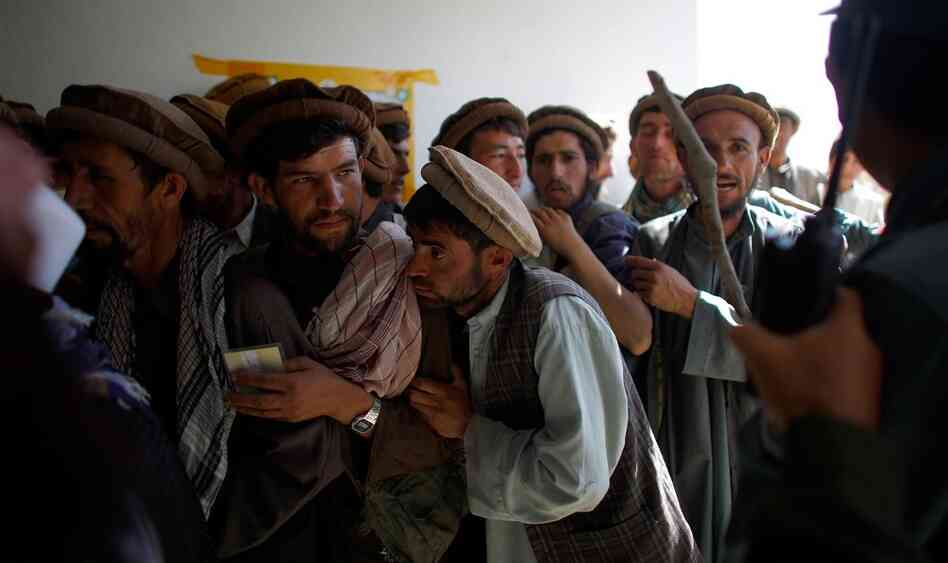 Afghan National Police try to control a line of men waiting to