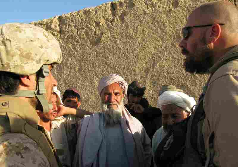 Retired New York City police officer Lt. Roger Parrino (right) talks with village elders in Khawji Jamal village. His beard makes Afghans view him as an elder among the Marines.