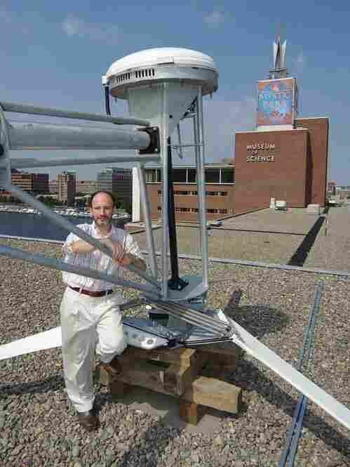 David Rabkin, Farinon Director for Current Science and Technology at the Museum of Science in Boston, stands on the museum's roof with the Proven 6 wind turbine that is yet to be installed. Credit: Museum of Science