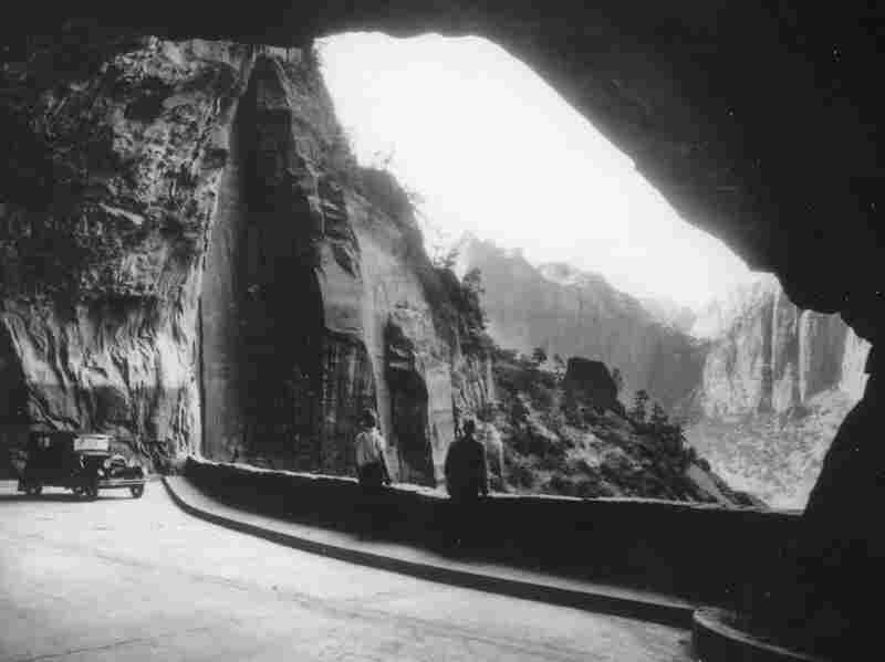 "In the early days of Zion Tunnel, drivers could park at vast ""windows"" blasted in the canyon walls and gaze out at the steep red rock cliffs of Zion National Park. Credit:  Utah State Historical Society"
