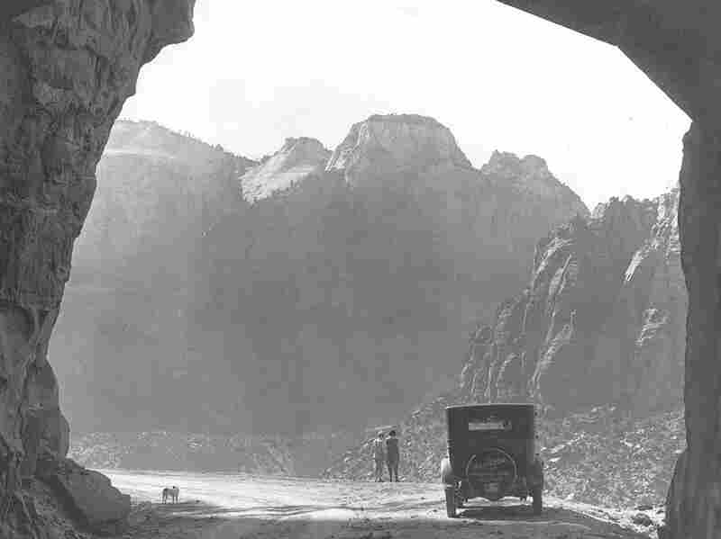 Early visitors stop at the west entrance of Zion Tunnel and take in the view. The tunnel itself is pitch black, except for the sections with windows, and pedestrians are prohibited. Credit: O.M. Uhl